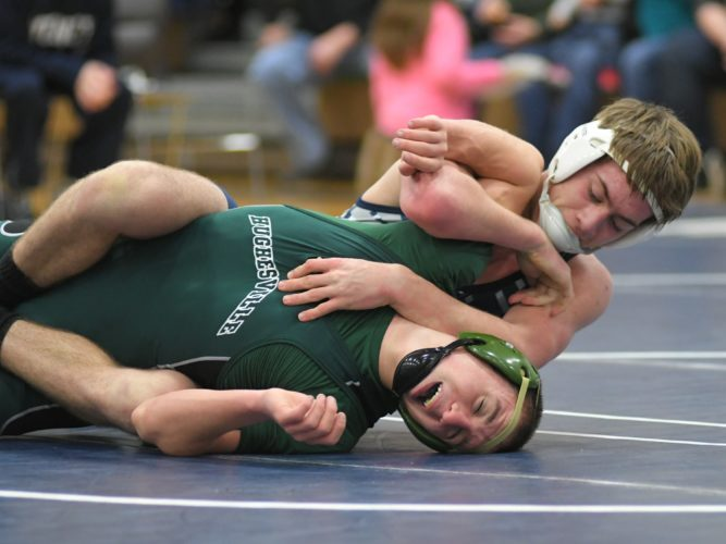 Muncy's Gaveyn Eisenhower works Hughesville's Caleb Dixon in a 15-4 major decision at 145 pounds Saturday at Muncy. View additional photos at cu.sungazette.com.