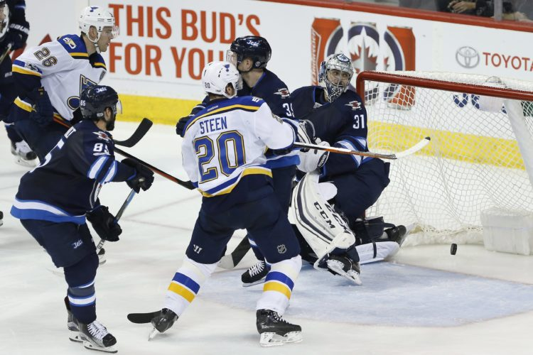 St. Louis Blues' Paul Stastny (26) scores on Winnipeg Jets goaltender Ondrej Pavelec (31) as Jets' Mathieu Perreault (85) and Toby Enstrom (39) and Blues' Alexander Steen (20) watch during the third period of an NHL hockey game in Winnipeg, Manitoba, Saturday, Jan. 21, 2017. (John Woods/The Canadian Press via AP)