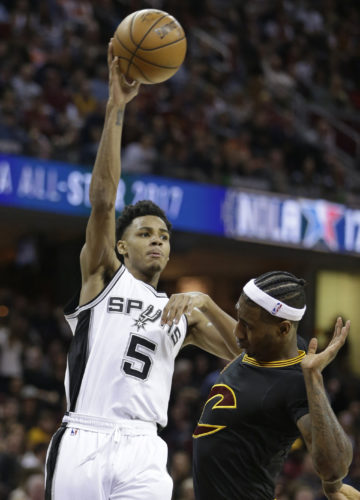 San Antonio Spurs' Dejounte Murray (5) passes over Cleveland Cavaliers' Iman Shumpert (4) in the first half of an NBA basketball game, Saturday, Jan. 21, 2017, in Cleveland. (AP Photo/Tony Dejak)