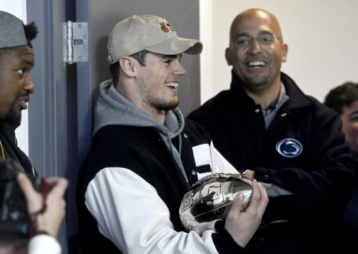 Penn State quarterback Trace McSorley laughs with teammates and coach James Franklin, right, as they wait to be introduced with the Big Ten title trophy at the Penn State hockey game against Ohio State, Friday, Jan. 20, 2017, in State College, Pa. (Abby Drey/Centre Daily Times via AP)