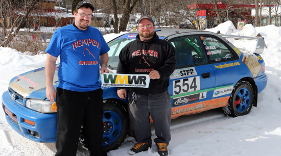 JOHN EATON/Sun-Gazette Correspondent Co-driver Chris Wimbrough, left, and driver Jeremy Keck are shown with Keck's 1999 Subaru Impreza. Keck will drive the Impreza during Saturday's Waste Management Winter RallySprint.