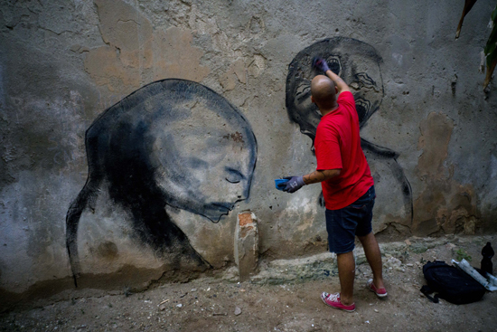 In this Feb. 9, 2017 photo, urban artist Yulier P. paints on a wall in Old Havana, Cuba. The works of the 27-year-old artist, whose full name is Yulier Rodr'guez PŽrez, are striking not just for their artistry and ubiquity, but the fact that they exist at all in a place where graffiti is rare. (AP Photo/Ramon Espinosa)