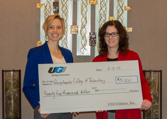 PHOTO PROVIDED Elizabeth A. Biddle, left, director of corporate relations for Penn College, accepts a gift of $25,000 from Ann Blaskiewicz, community relations manager north for UGI Utilities. The gift supports the college Penn College NOW and SMART Girls programs, both of which promote technology education for high school students.