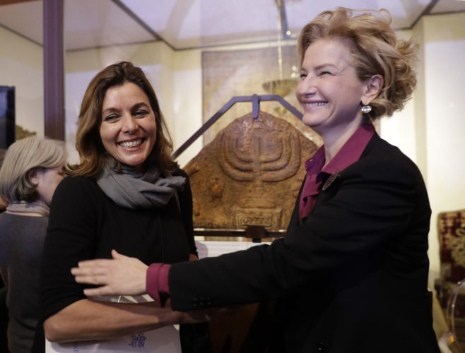 ASSOCIATED PRESS Director of the Vatican Museums, Barbara Jatta, left, and Director of Rome's Jewish Museum Alessandra Di Castro pose in front of a bas-relief showing a menorah at the end of a press conference in Rome on Monday. The Vatican and Rome's Jewish community are teaming up for the first- ever joint exhibit by the two institutions' museums. The focus will be the menorah, depicted in both Jewish and Catholic art, over the centuries.