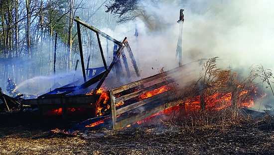 PHILIP A. HOLMES/Sun-Gazette Flames rip through a collapsed storage trailer, one of two vacant structures that were leveled by a fire that broke out on Tallman Hollow Road about 5 miles from Montoursville at 3:30 p.m. Monday.