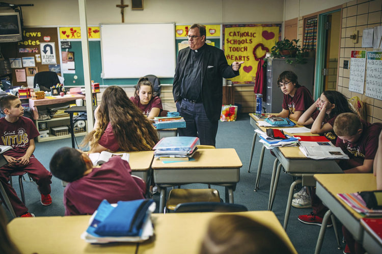 ASSOCIATED PRESS In this Feb. 7 photo, the Rev. Frank D. Almade talks to students at St. Vitus Catholic School in New Castle. Almade is the pastor of parishes in New Castle, Mary Mother of Hope, St. Joseph the Worker, St. Vincent de Paul and St. Vitus.