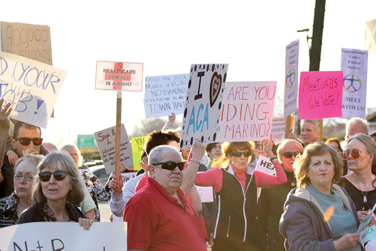 ANNE REINER/Sun-Gazette  A crowd of protesters stand outside the district office of U.S. Rep. Tom Marino, R-Cogan Station, on Commerce Park Drive to ask him to hold a town hall for constituents in his district Friday evening.