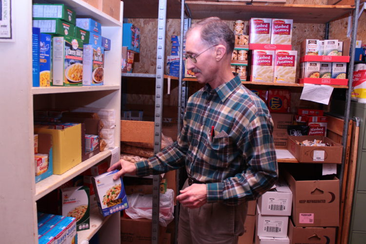 MEGAN BLOOM/Sun-Gazette John Aderhold, of Williamsport, has spent the majority of his life helping others fulfill basic needs such as food, water and spiritual nourishment. Each week he takes time to run the West End Christian Community Center Food Bank. Above, Aderhold stocks shelves.