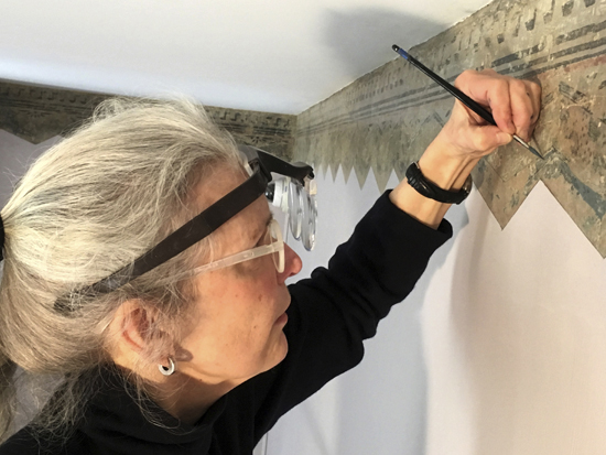 In this Feb. 27, 2017 photo, art restoration expert Margaret Saliske works on hand-painted borders at the home of artist Thomas Cole, in Catskill, N.Y. Not only did Cole paint mountainous landscapes that defined the Hudson River School. He painted on his parlor walls in Catskill. The decorative patterns near the ceiling lines, hidden under layers of paint for more than a century and discovered a few years ago, will be fully displayed when the Thomas Cole National Historic Site opens for the season in May.  (AP Photo/Michael Hill)