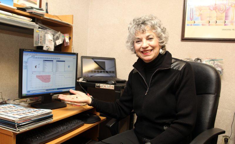 KAREN VIBERT-KENNEDY/Sun-Gazette Elvira Ferraro, owner of Beltone Hearing Aid Services, holds a hearing aid in the testing room at Beltone on West Fourth Street.