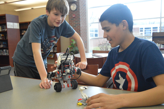 KATELYN HIBBARD/Sun-Gazette Eighth graders Jay Oaks, left, and Sam Rosario test the gyrobot's balance by moving it away from its stand and seeing how long it can move about on its own.