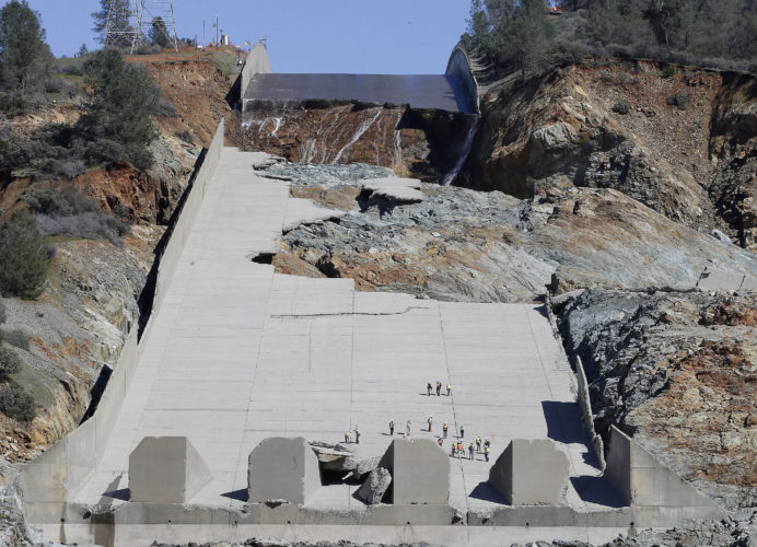 "ASSOCIATED PRESS FILE PHOTO In this Feb. 28 photo, officials inspect Oroville Dam's crippled spillway in Oroville, Calif. A team of experts is warning of a ""very significant risk"" if the main spillway of the California dam is not operational again by the next rainy season. The warning is contained in a report obtained by The Associated Press."