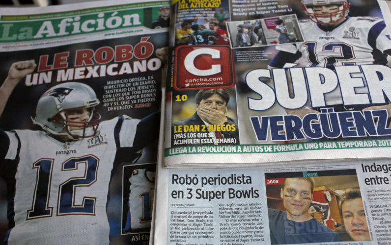 "Front pages of Mexican newspapers show headlines and photos about the Tom Brady Super Bowl jersey that was allegedly stolen by a Mexican journalist, bottom right on a selfie with Brady, in Mexico City, Mexico, on March 21. The headlines read in Spanish ""Super embarrassment"" top right and ""Was stolen by a Mexican,"" left.  (AP)"