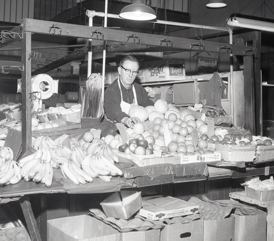 SUN-GAZETTE FILE PHOTO The Market House was a hot spot for Saturday morning shopping in Williamsport from the early 1930s until the curbstone market went out of existence in the early 1970s. Here, a worker at a produce stand arranges fruit.