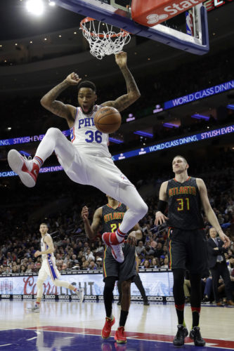 The Philadelphia 76ers' Shawn Long reacts after a dunk past the Atlanta Hawks' Mike Muscala (31) and Kent Bazemore (24) during the first half on Wednesday in Philadelphia. (AP)