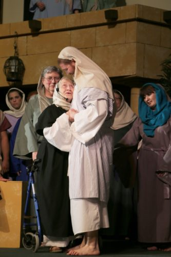 Photo courtesy of MICHELLE PETERS Photography Pictured, Jesus (Jared Moore) heals the crippled woman (Marge Haagen), oldest cast member at age 92.