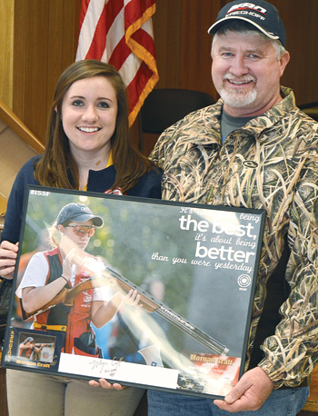 PAT CROSSLEY/Sun-Gazette Correspondent Morgan Craft and her dad, Dave, who also was one of her first shooting coaches, display a poster honoring her during the Consolidated Sportsmen of Muncy Creeks' recent annual banquet.