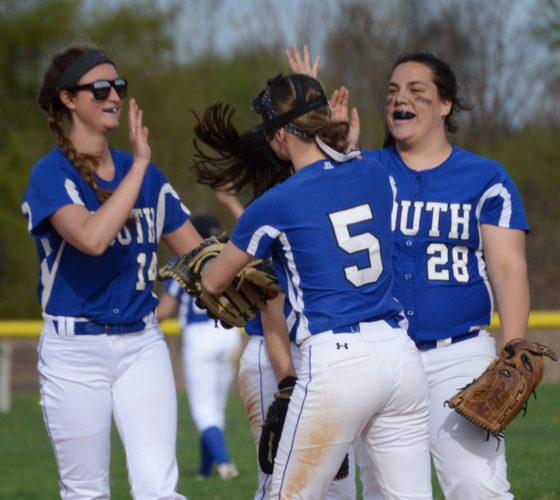 KATELYN HIBBARD/Sun-Gazette Paige Lentz, 14, Isabella Bachman, 5, and pitcher Emily Hennigan, 28, congratulate each other after taking out two Hughesville runners in one play Monday at South Williamsport.