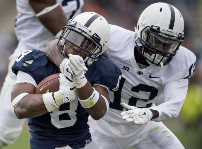 Penn State running back Mark Allen gets stopped by Desi Davis during the Penn State Blue-White spring game in State College on Saturday. (AP)