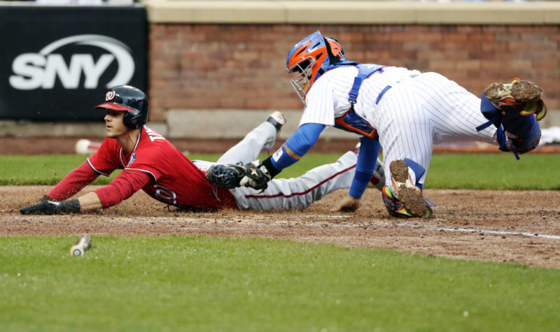 The Washington Nationals' Trea Turner, left, slides past New York Mets' catcher Rene Rivera, right, to score during the fifth inning. (AP)
