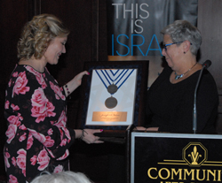 CARA MORNINGSTAR/Sun-Gazette Dr. Davie Jane Gilmore, president of Pennsylvania College of Technology, right, presents the Israel Unity Award to Jennifer D. Wilson, president and CEO of First Community Foundation Partnership of Pennsylvania, left, during the Central Pennsylvania State of Israel Bonds Annual Award Dinner at the Community Arts Center in Williamsport on Sunday.