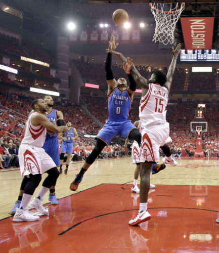 The Oklahoma City Thunder's Russell Westbrook (0) shoots as the Houston Rockets' Clint Capela (15) defends during the first half in Game 5 on Tuesday in Houston. (AP)