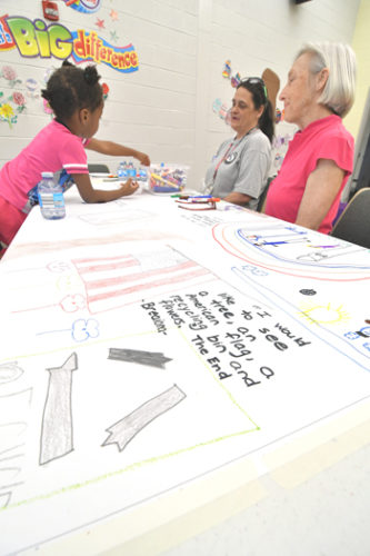 "MARK NANCE/Sun-Gazette Kathleen Carpenter of Americorps, middle, and volunteer Julie Hulslander assist Miasia Poole5, daughter of Star Poole of Williamsport as she works on her part on the muras on ""What children want to see in the ideal city"" during  the Heart of Williamsport's Summit Up! Community Celebration of What We Value at Cochran Elementary School Wednesday."