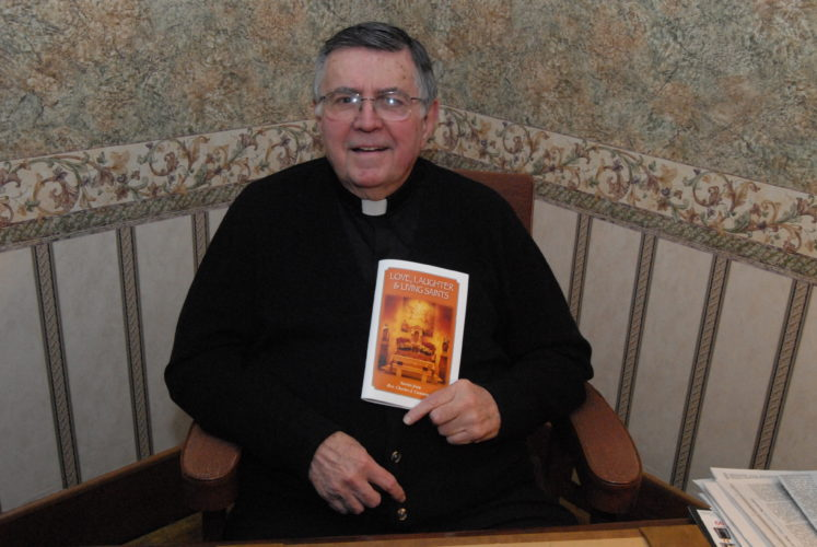 The Rev. Charles J. Cummings, of Jersey Shore, has a copy of his book, 'Love, Laughter and Living Saints,' at his home in Jersey Shore recently. CARA MORNINGSTAR/Sun-Gazette