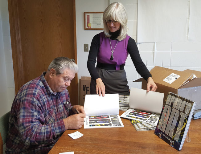 """Courtesy Photo Bruno Hirzel autographs copies of his just published book, """"Bruno's Art,"""" as Besser Museum Executive Director Chris Witulski looks on.  He donated 50 copies of the book for the museum to sell as a fundraiser."""