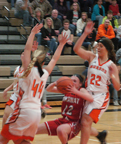 News Photo by Jonny Zawacki Rogers City's Taylor Fleming (22) and Sydney Purgiel (44) reject a shot attempt from Onaway's Kennedy Crawford (12) during the first quarter of a girls basketball game on Wednesday at Rogers City High School.