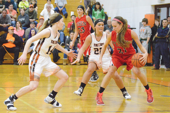 News Photo by James Andersen Posen's Sam Lenard (21) is guarded by Hillman's Lyndsey Ryba (14) and Brooke Jones as she dribbles up the court during a girls basketball game on Friday at Hillman High School.