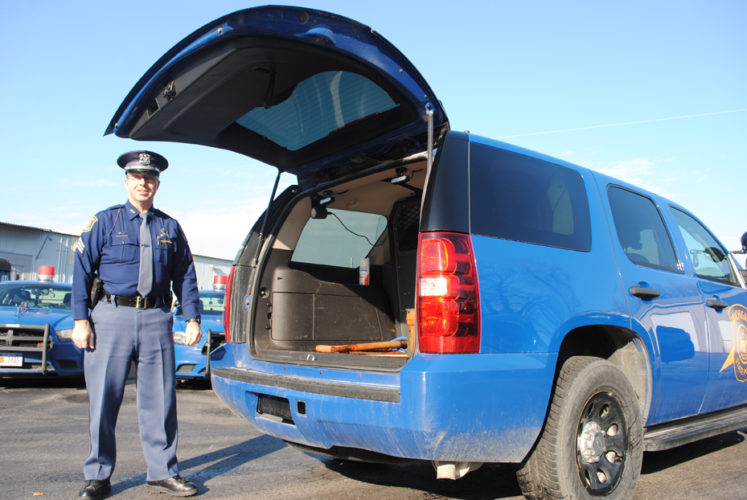 "News Photo by Jason Ogden Michigan State Police Sgt. John Richards shows the back end of an MSP ""blue goose"" a nickname for the agency's patrol vehicles. Troopers are asking the public to help fill a ""blue goose"" with food and toy donations during an event to be held Saturday at both Walmart and Neiman's Family Market in Alpena."