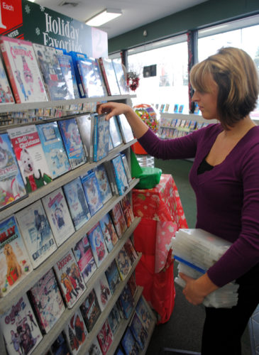 News Photo by Jason Ogden Alpena Family Video Manager Katie Larsen stocks the Christmas section Tuesday at the video store. She said as Christmas approaches holiday favorites are harder and harder to rent at the store.