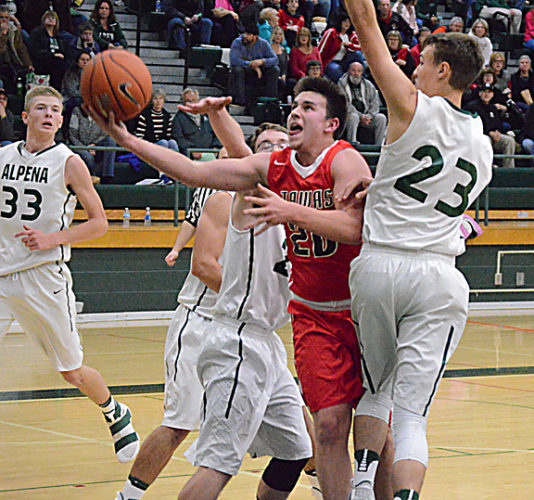 News Photo by Jonny Zawacki Tawas guard Owen Irvin (20) splits Alpena defenders Cam DeCaire (23) and Isaac Jore and scores on a layup during the first quarter of a basketball game on Tuesday at Alpena High School.