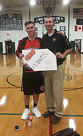 Couresty Photo Hillman's Gunnar Libby celebrates with coach Eric Muszynski after scoring his 1,000th career point in a victory over Cedarville on Tuesday. Libby poured in a game high 30 points in the win.
