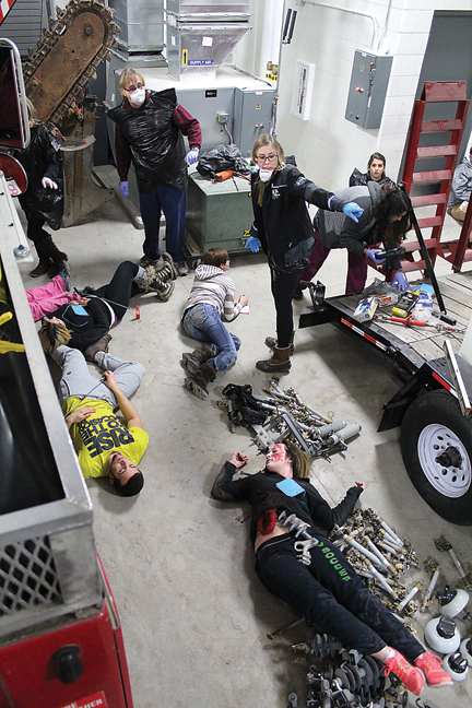News Photo by Jordan Spence RIGHT: Alpena Community College registered nursing students help direct where they need to take victims, during the simulated terrorist sitaution Friday.