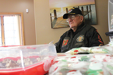 News Photo by Jordan Spence  Vietnam Veterans Chapter 583 President Wayne Trapp helps with a bake sale at Thunder Bay Credit Union in Alpena Thursday. The bake sale helped raise money for Operation Toys For Kids organized by the veterans.