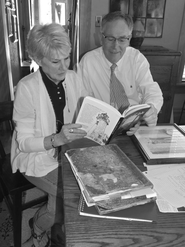Brother and sister Janet and Bob Young look through one of the local Grand Lake history books she has written. Bob, owner of Young's Appliance and Young's ArtVan in Alpena, did many of the illustrations for her books.