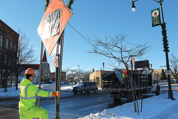 News Photo by Steve Schulwitz Alpena Department of Public Works employee Justin Weaver sets up a detour sign that will help to guide motorists around the Second Avenue Bridge, which will be close Monday until the end of the month. The bridge work is expected to wrap up in June.