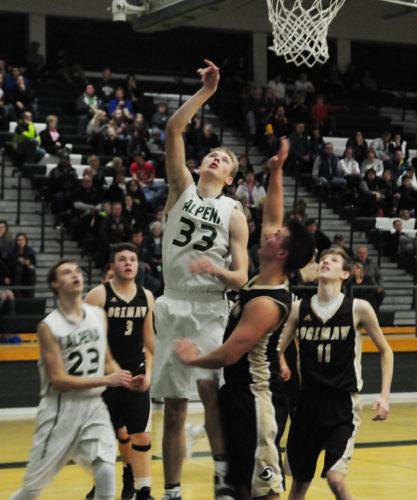 News Photo by Jonny Zawacki Alpena's Chris Derocher (33) scores a basket over Ogemaw defender Garrett Paulson during the third quarter of a boys basketball game on Friday at Alpena High School.