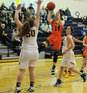 News Photo by Jonny Zawacki Hillman's Lyndsey Ryba (14) takes a running jump shot over Alcona's Brittany Decker (50) during the third quarter of a North Star League girls basketball game at Alcona High School on Monday night.