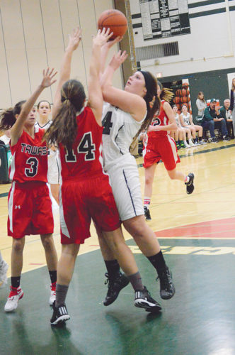 News Photo by James Andersen Alpena's Dakota Prevo, right, puts up a shot while being defended by Tawas players Carley Bolen (3) and Kayla Costigan during the first half of a girls basketball game at Alpena High School on Thursday.