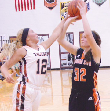News Photo by James Andersen Hillman Vanessa Schook, left, attempts to block Rogers City's Hannah Fleming's three-point attempt during the second half of a girls basketball game on Friday in Hillman.