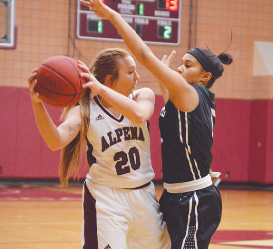 News Photo by James Andersen Alpena Community College's Kelsey Huffman (20) looks for a teammate to pass to while being guarded by Oakland's Alisha McCain during a women's basketball game Saturday at Park Arena.