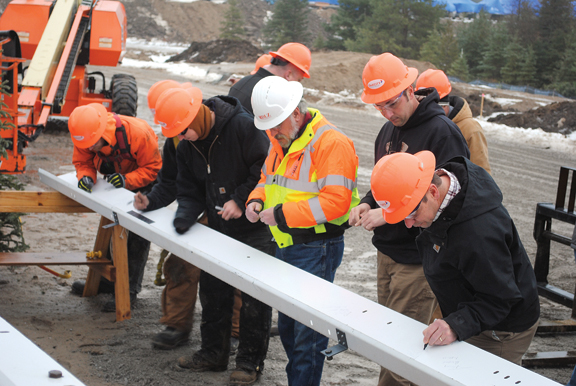 "News Photo by Jason Ogden Members of OakCity Contracting use felt-tipped pens to sign their name and date on the last piece of the new Thunder Bay Transportation Authority building Monday. The piece was erected on the building as part of the ""topping off"" ceremony."