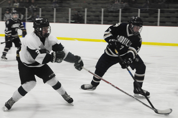 News Photo by James Andersen Alpena's Colby Plowman (3) battles with Cadillac's Justin Smith (7) for a loose puck during the first period of a Big North Conference hockey game on Friday at Northern Lights Arena.