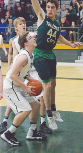 News Photo by James Andersen Alpena's Isaac Jore prepares to shoot while being defended by Traverse City West's Caleb Corwin (44) during a boys basketball game at Alpena High School on Friday.