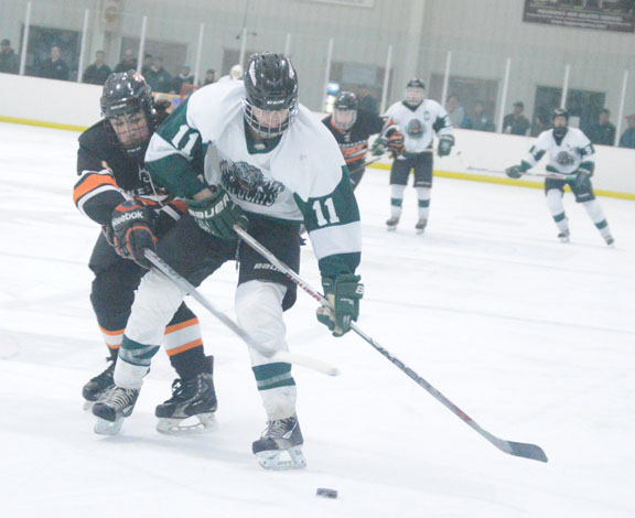 News Photo by James Andersen Alpena's Lars MacArthur fights for control of the puck against Cheboygan's Max Paull during the first period of a hockey game on Tuesday at Northern Lights Arena.