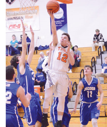 News Photo by James Andersen Hillman's Gunnar Libby (12) drives to the basket between several Oscoda defenders during a boys basketball game on Wednesday in Hillman.