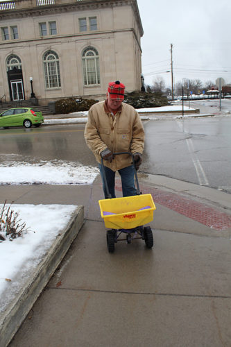 News Photo by Jordan Spence  Carl Kasubowski salts the sidewalk outside of the Alpena County Library Friday.